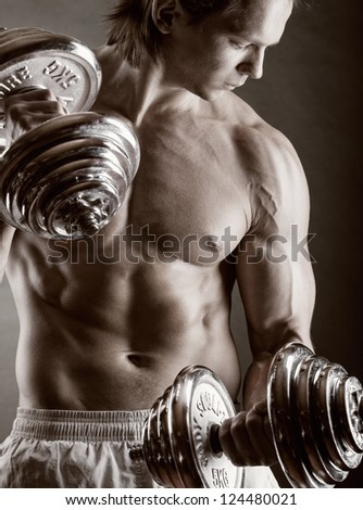 Young muscular man with dumbbells on black background - stock photo