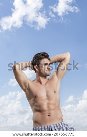 Young muscular man with hands behind head against cloudy sky - stock photo