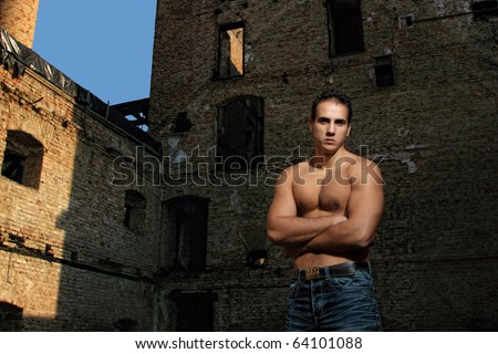 Young muscular sexy male model against retro vintage outdoor background - stock photo