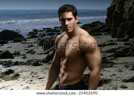 Young muscular shirtless man on beach with dramatic lighting sculpting his form - stock photo