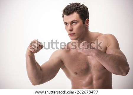 Young muscular sports guy with naked torso clenched fists ready to punch. - stock photo