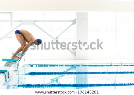 Young muscular swimmer in low position on starting block in a swimming pool - stock photo