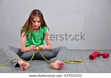 Young muscular teenage girl sitting on the floor with skipping rope and dumbbells relaxing having rest in studio. - stock photo
