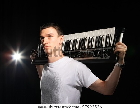 young musician, a pianist on the black background - stock photo