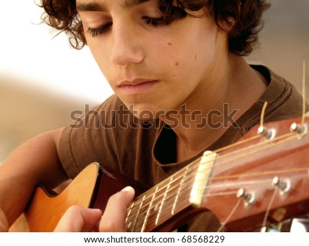 Young Musician Closeup: closeup shot of a 15 year old musician with acoustic guitar, very concentrated on his music. Selective focus. - stock photo