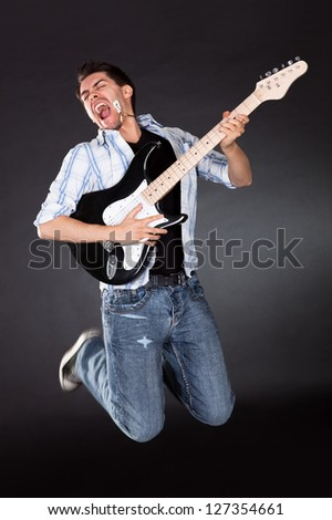 Young musician jumping with his guitar while singing
