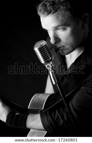 young musician playing a guitar and singing - stock photo