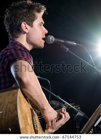 young musician playing acoustic guitar and singing, concert photo, for music and entertainment themes - stock photo