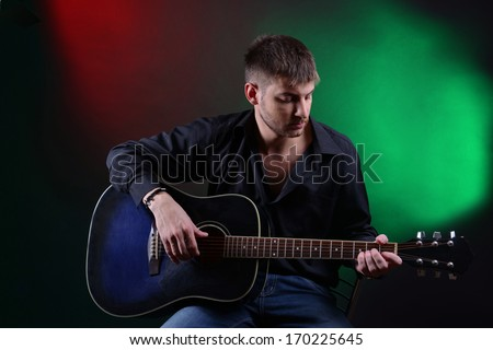 Young musician playing acoustic guitar and singing, on dark color background - stock photo