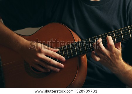 Young musician playing acoustic guitar close up - stock photo