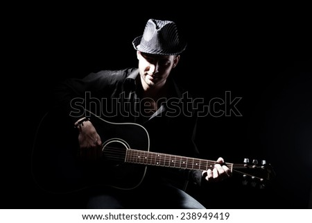 Young musician playing acoustic guitar, on dark background - stock photo