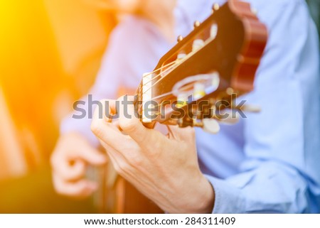 Young musician playing at acoustic guitar - stock photo