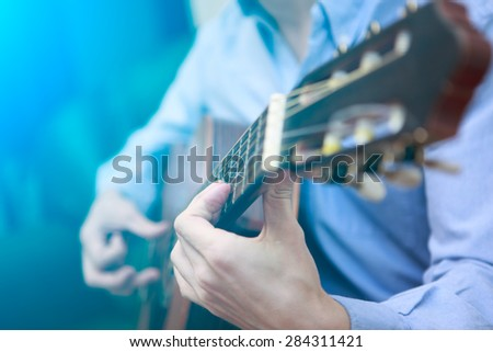 Young musician playing at acoustic guitar. Blue lensflare - stock photo