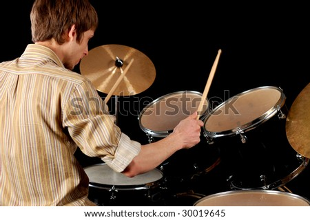 Young musician playing drums isolated on black. - stock photo