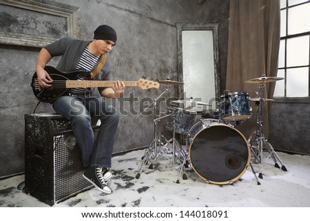 Young musician plays bass electric guitar sitting on amplifier in room powdered with snow - stock photo