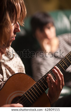 Young Musician Plays His Acoustic Guitar as Friend in the Background Listens. - stock photo