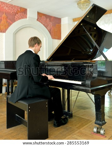 Young musician plays on black grand piano - stock photo