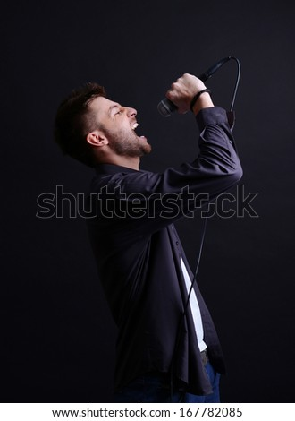 Young musician singing, on gray background