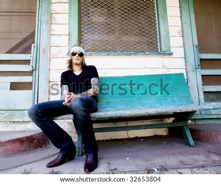 Young musician sitting in front of an abandoned house. - stock photo