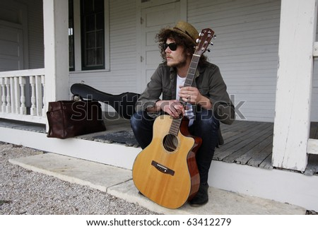 Young musician sitting in front of an abandoned house, holding a guitar.