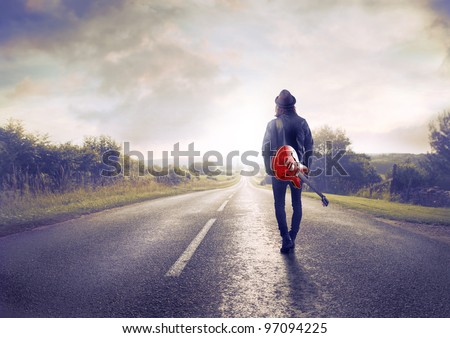 Young musician walking on a countryside road with a guitar on his shoulder - stock photo
