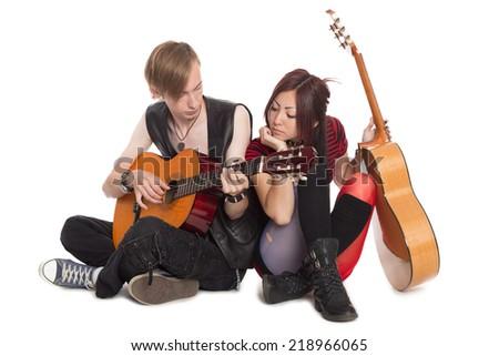 Young musicians play guitars. Interracial young couple, Asian woman and Caucasian man. - stock photo