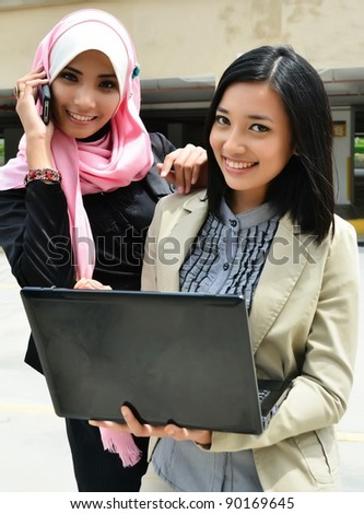 young muslim business woman in head scarf with cell phone and laptop