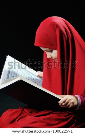 Young muslim girl reading holy koran - stock photo
