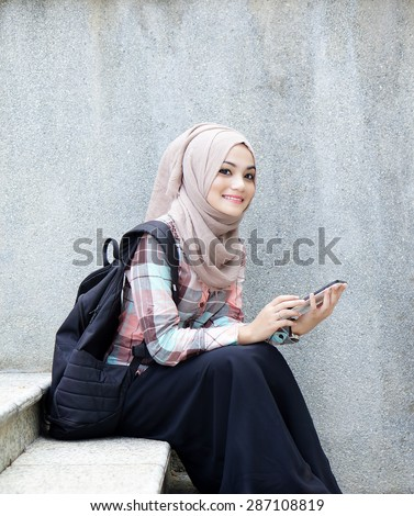young muslim girl student with her tablet - stock photo