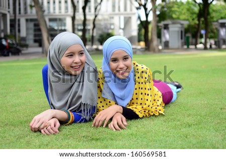 Young muslim girl wearing hijab lying on grass - stock photo