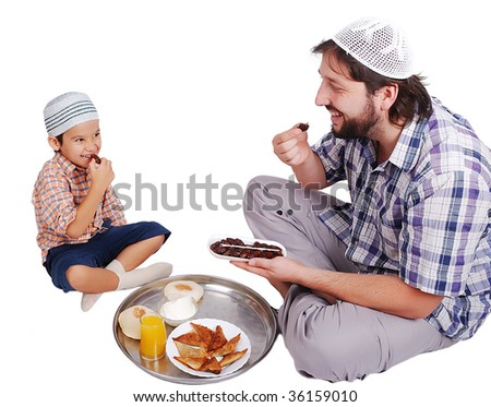 Young muslim man and his son with prepared food for iftar in Ramadan - stock photo
