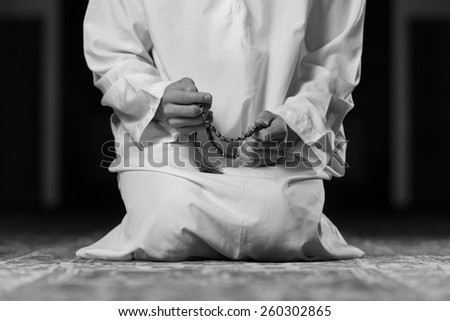 Young Muslim Man Making Traditional Prayer To God While Wearing A Traditional Cap Dishdasha - stock photo