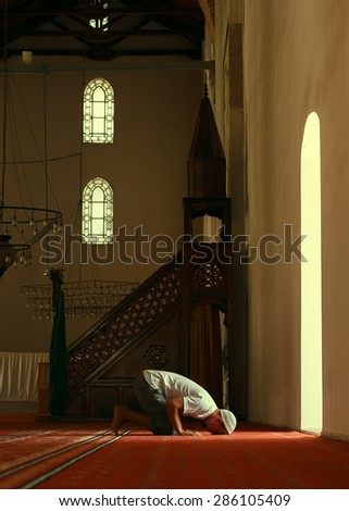 Young muslim man praying in mosque by the window - stock photo