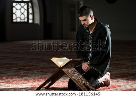 Young Muslim Man Reading The Koran - stock photo
