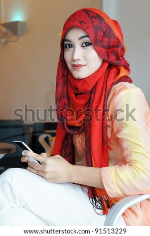 Young muslim stylish women writing text messaging at a cafe looking to camera - stock photo