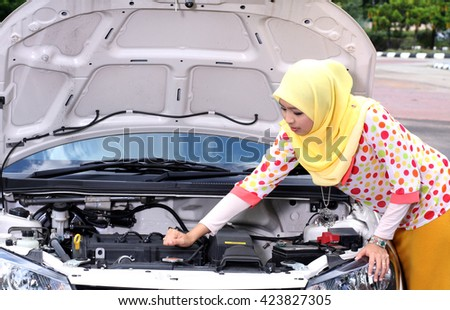 Young muslim woman checking engine on his car