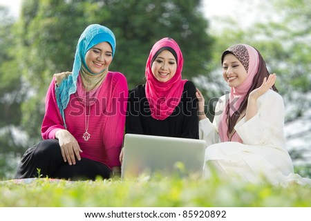 young muslim woman happy using laptop with friends - stock photo