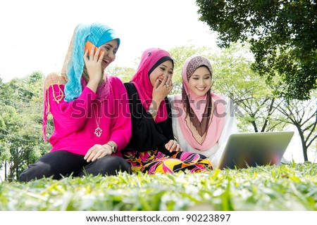 young muslim woman happy using laptop with friends