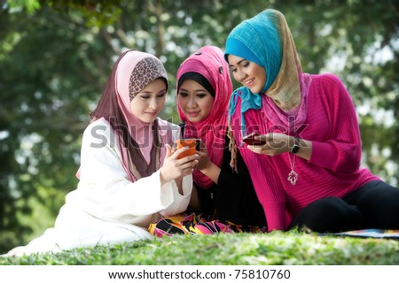 young muslim woman in head scarf meet friends and using phone in the park - stock photo