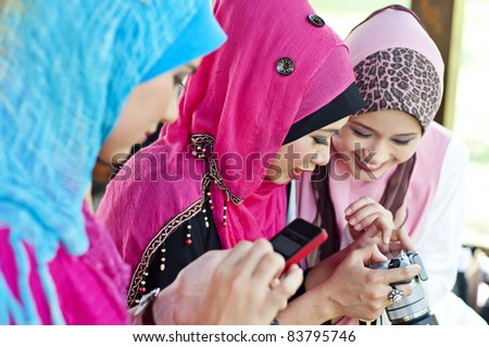 young muslim woman in head scarf using camera and handphone with friends - stock photo