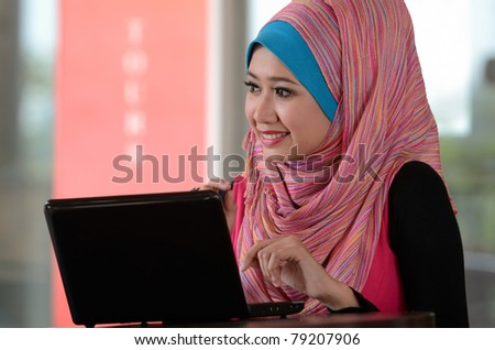 young muslim woman in head scarf using laptop in cafe - stock photo