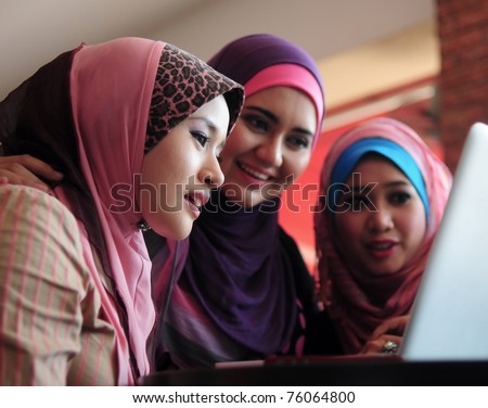young muslim woman in head scarf using laptop in cafe with friends - stock photo