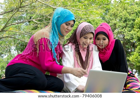 young muslim woman in head scarf using laptop with friends