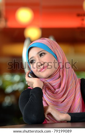 young muslim woman in head scarf using phone in cafe - stock photo