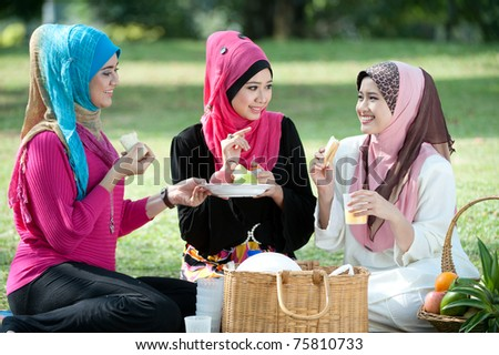 young muslim woman in head scarf while relaxing and eating with friends in the park