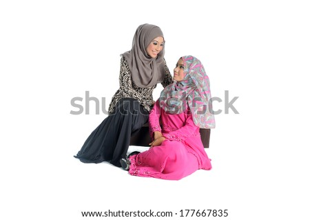 young Muslim woman in head scarf with modern clothes talk to her sister , isolated on white - stock photo