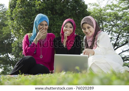 young muslim woman in hijab happy looking at laptop with friends - stock photo
