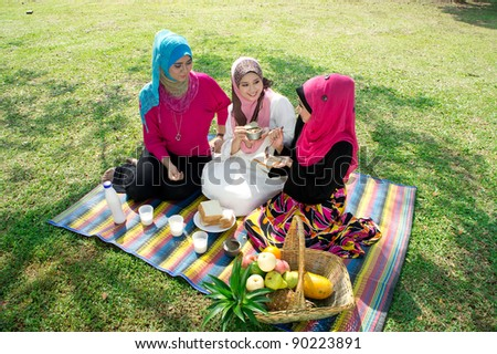 young muslim woman in hijab while relaxing and eating with friends in the park - stock photo