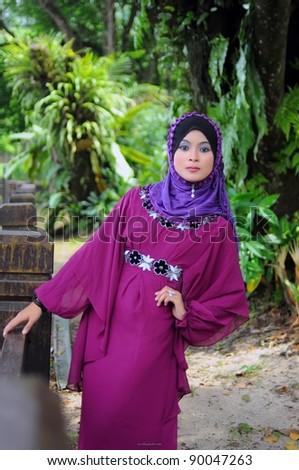 young muslim woman in purple head scarf  wearing hijab - stock photo