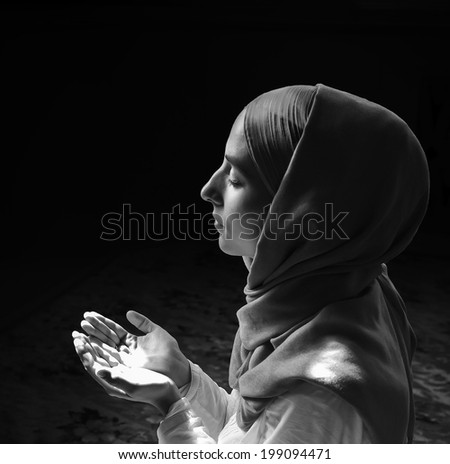 Young muslim woman praying in mosque. Monochrome - stock photo